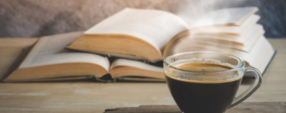 Black coffee with old books on wood table